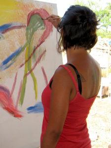 Malschülerin malt an der Staffelei ein abstraktes Bild mit Acrylfarben.