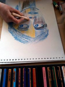 Schülerin zeichnet mit Wassermalkreiden ein Frauenportrait.
