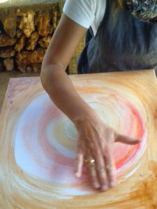 Malschülerin malt mit Naturfarben und Pigmenten gestisch mit der Hand.
