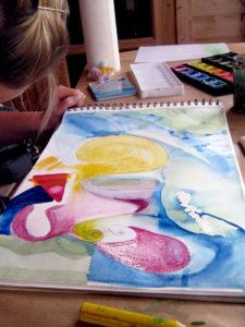 Malschülerin macht Formstudien mit Wasserfarben und-kreiden.