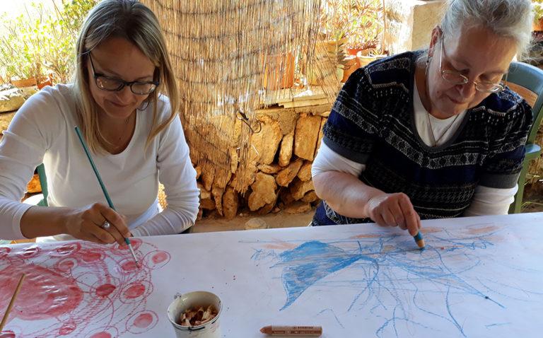 Zwei Malschülerinnen zeichnen auf dem mit Papier bespannten Maltisch.