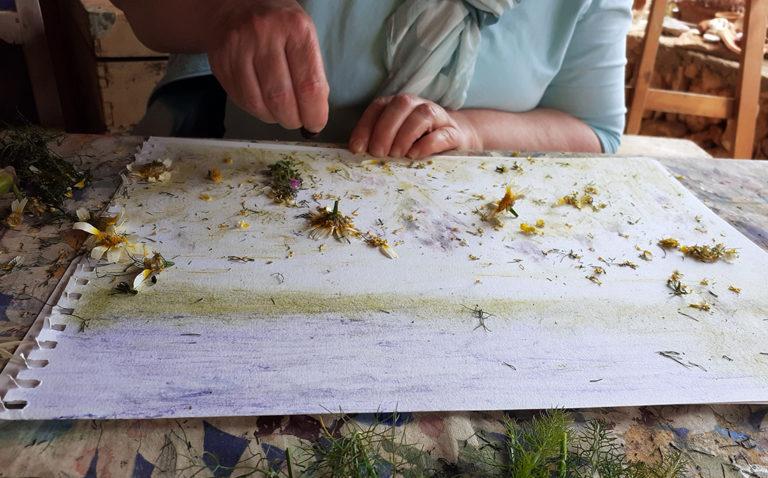 Malschülerin experimentiert mit Pflanzenpigmenten.