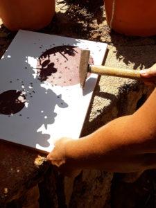 Malschülerin experimentiert mit Erdfarbe und Hammer