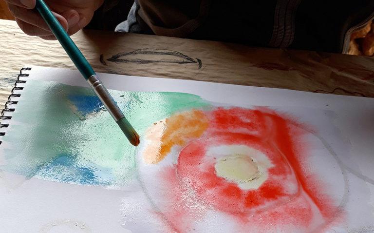 Kursteilnehmerin malt abstrakt mit Wasserfarben.
