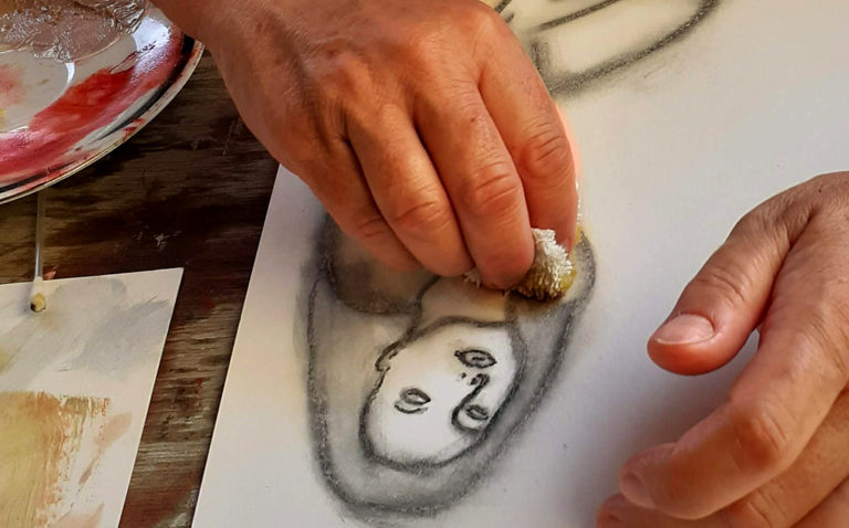 Malschülerin arbeitet mit Kreide und Kohle an einem Frauenakt.