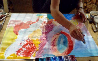 Malschülerin malt abstrakt und bunt mit Wasserfarben, Acryl und Kreide.